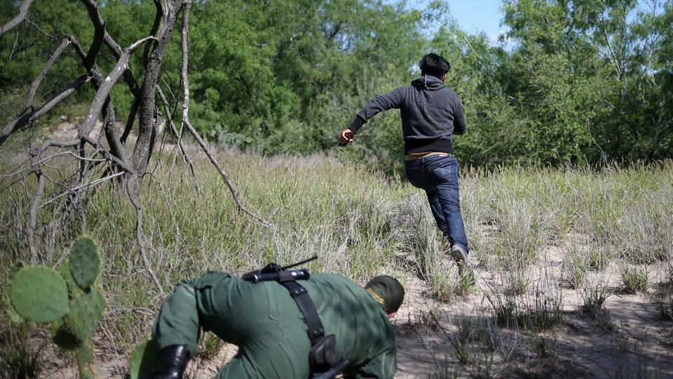 A man who illegally crossed the Mexico-US border evades a US Border Patrol agent near McAllen, Texas. (Loren Elliott / REUTERS)