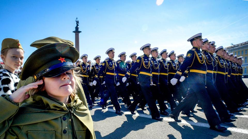 A girl dressed in a Soviet Army styled uniform salutes as Russian military personnel march at Dvortsovaya Square during the Victory Day military parade in Saint Petersburg, Russia. (Olga Maltseva / AFP)