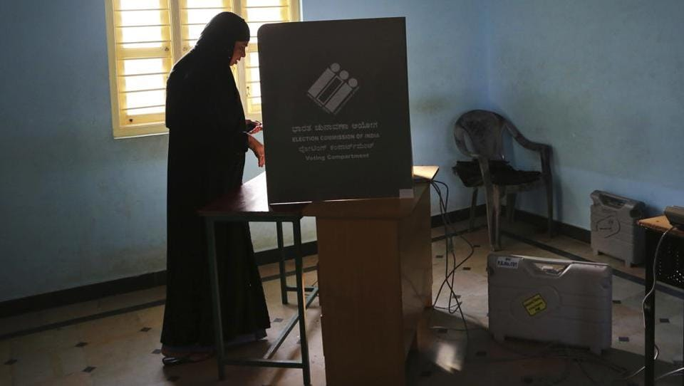 A woman casts her vote at a polling station in Bengaluru on Saturday. According to the election commission, as of 3pm, the voting percentage in the elections had reached 53% as voters lined up to choose their representatives after a high-stakes campaign. From all-women managed 'pink booths' to the use of third generation Electronic Voting Machines, the assembly elections in 2018 were marked by several firsts. (Aijaz Rahi / AP)