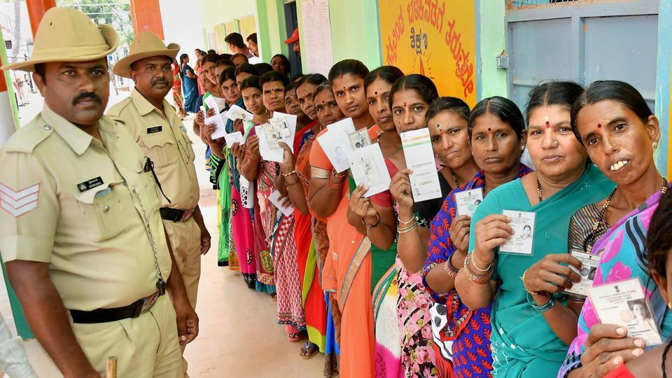 Voters stand in a queue with their voting IDs at a polling booth during the Karnataka assembly elections 2018, at Hundi village in Mysore on Saturday.