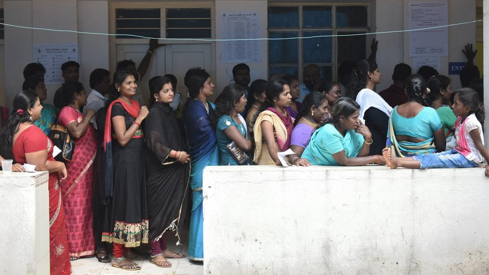 Voters stand in queue at a polling booth during the Karnataka assembly elections 2018 in Bengaluru.