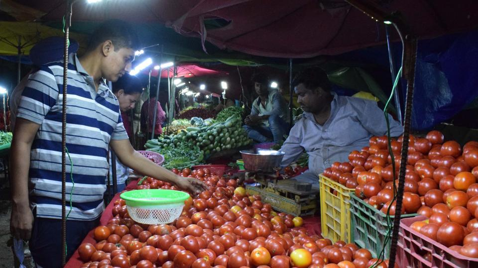 A man purchases tomatoes at Aapni Mandi at sector 40 in Chandigarh on Saturday.