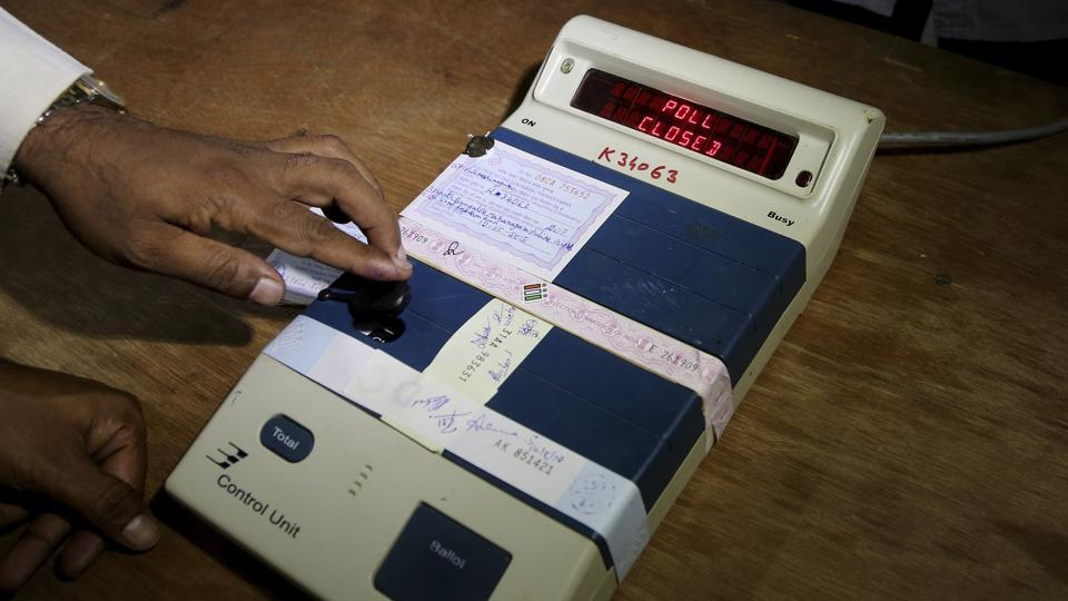 An election officer closes an electronic voting machine at the end of polls at a polling station in Bangalore on Saturday.