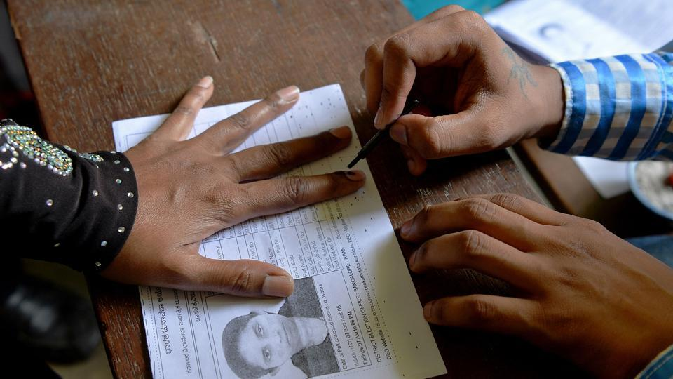 An election official puts indeliable ink on the finger of a voter before she casts her ballot in the Karnataka assembly elections at a polling station in Bangalore on May 12, 2018.