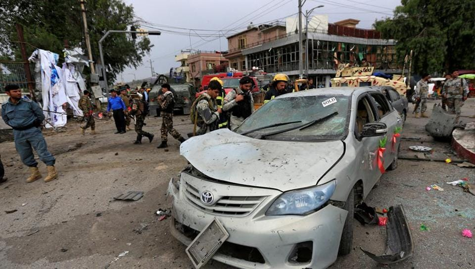 Afghan security forces inspect a damaged vehicle after blasts in Jalalabad city.