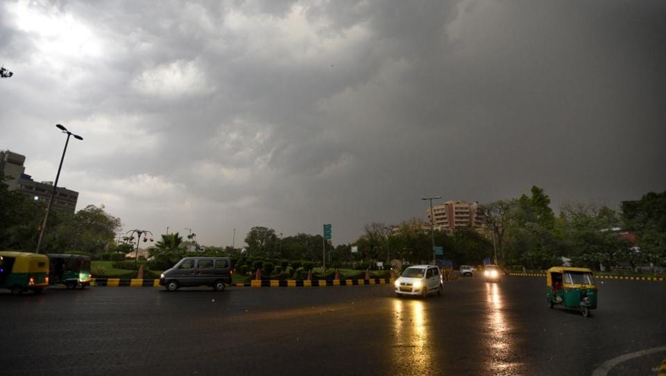 Cars on a drenched Delhi road after rain and a dust storm, at Mandi House in the national capital on Sunday.