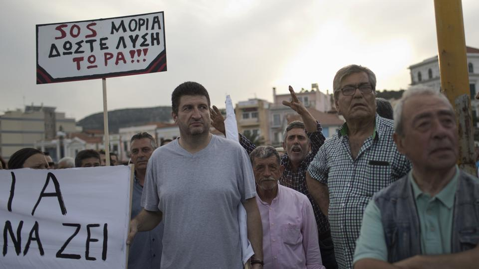 "Islanders hold a placard which reads in Greek ""SOS Moria. Solution now"", in a protest during a visit by Greek Prime Minister Alexis Tsipras. Residents complain about petty crimes that have risen since the camps opened, and others say their good will toward people fleeing war had been exploited by Greek and European policymakers. (Petros Giannakouris / AP)"