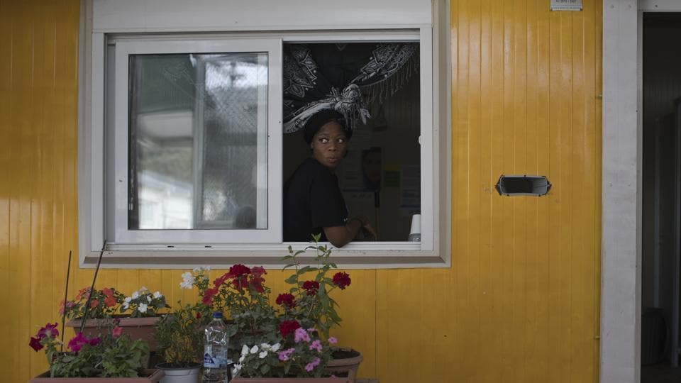 "A woman looks out of a window of a prefabricated house in the sector of Moria Camp reserved to single women travelling alone. ""We saw dozens of men with papers in their hand saying they were suffering from depression, anxiety disorders, and had suicidal dispositions; terrified women at risk of sexual violence in a European country that should be providing them with safety,"" Spatharidou said. (Petros Giannakouris / AP)"