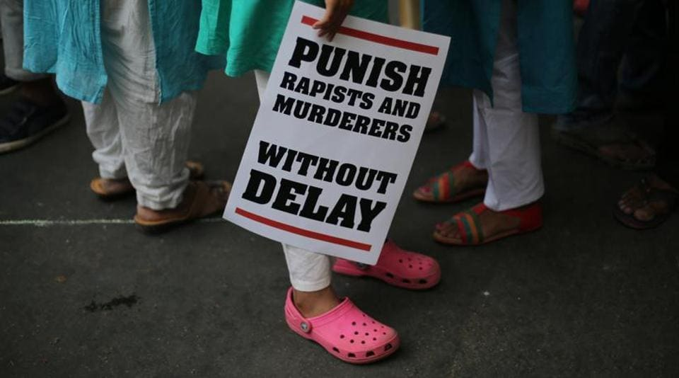 A protestor stands with a placard during a demonstration against incidents of rape, in New Delhi.