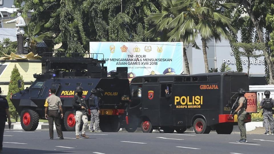 Police vehicles are parked outside local police headquarters following an attack in Surabaya, East Java, Indonesia, Monday, May 14, 2018.