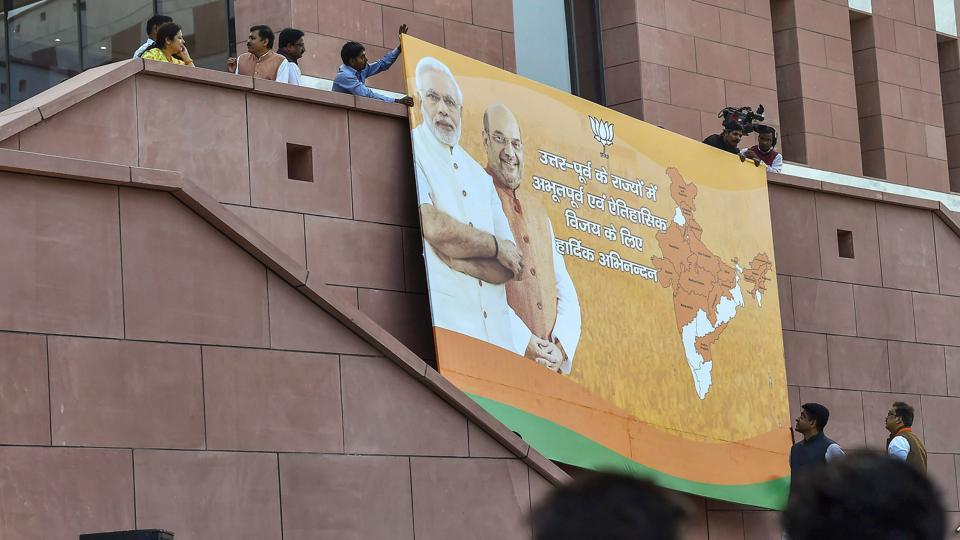 BJP party workers set up a poster of Prime Minister Narendra Modi and BJP president Amit Shah at party headquarters in New Delhi.