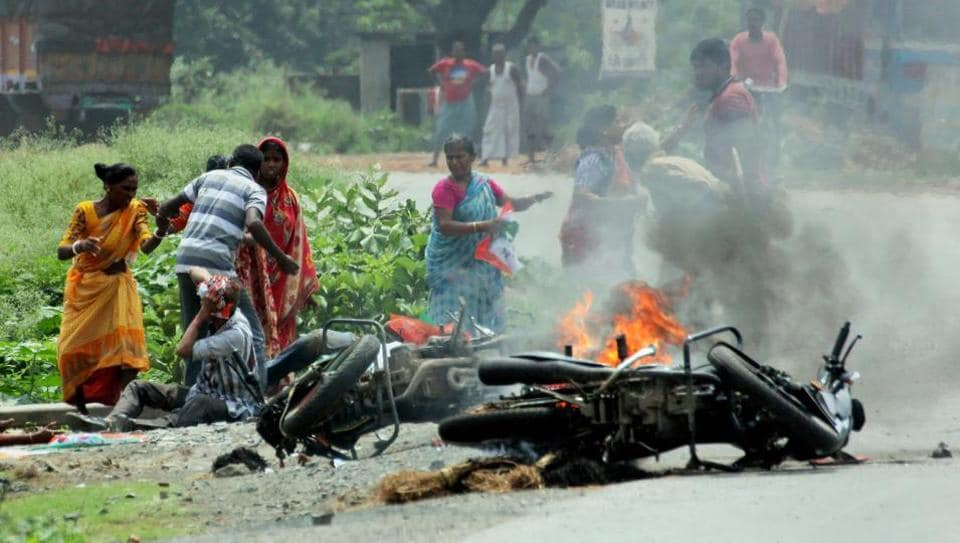People injured in poll violence sit by the side of a road as a vehicle is set on fire during the panchayat polls, in Nadia district of West Bengal.