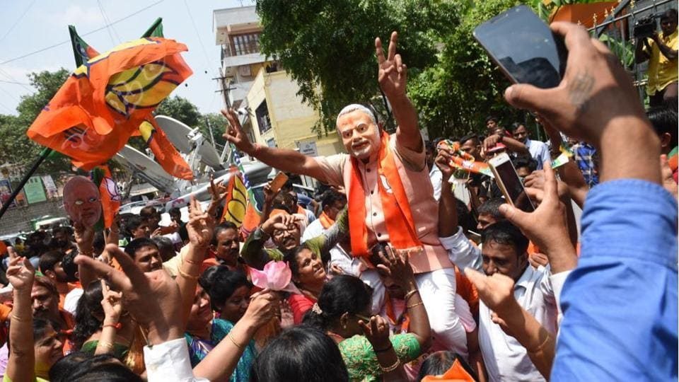 A supporter of Bharatiya Janata Party (BJP) wearing a mask of Prime Minister Narendra Modi flashes victory sign as he celebrates early leads for the party in the Karnataka state elections in Bengaluru. The BJP has taken a big lead over the Congress in the Karnataka election results and touched the halfway mark by noon, counting of votes showed on Tuesday. (Arijit Sen / HT Photo)