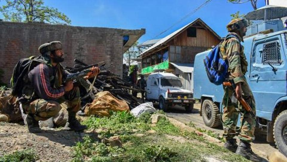 Security personnel stand guard during an encounter between security forces and militants in South Kashmir