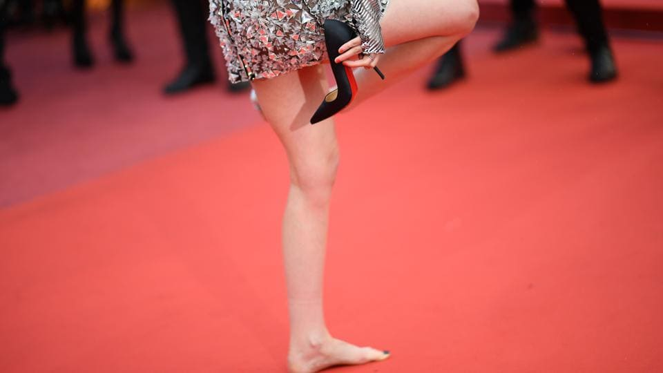 US actor and member of the Feature Film Jury Kristen Stewart removes her shoes on the red carpet as she arrives on May 14, 2018 for the screening of the film BlacKkKlansman at the 71st edition of the Cannes Film Festival.