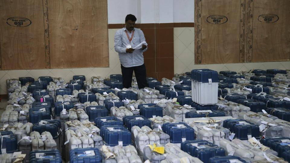 A polling official stands next to electronic voting machines in Bangalore. Counting of votes took an interesting turn late on Tuesday, with the BJPfalling short of majority despite an impressive showing and the Congress reaching out to the JD(S) to keep PMNarendra Modi's party at bay.
