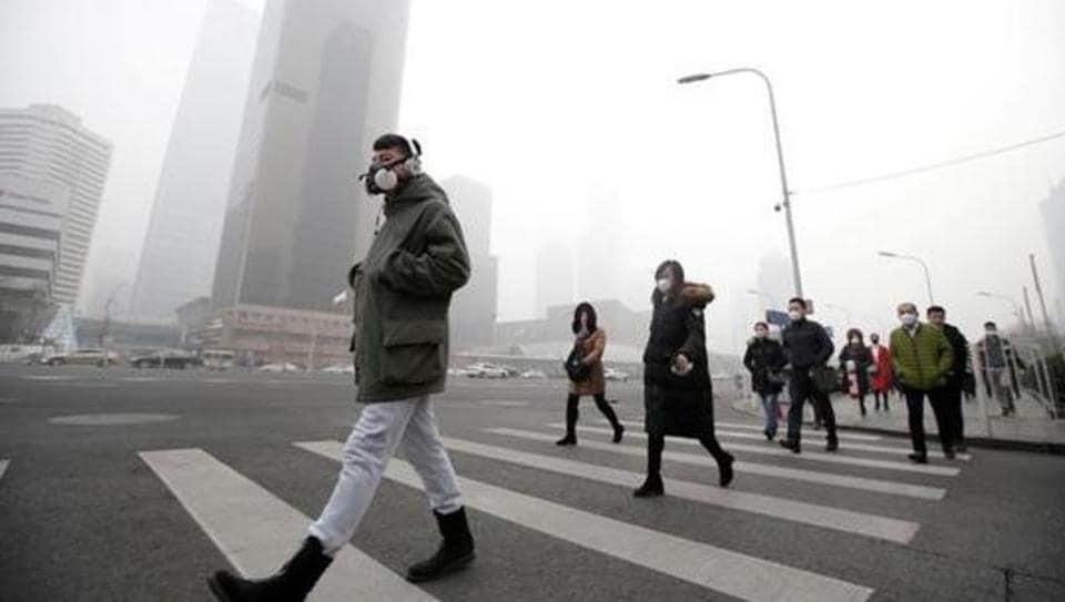 Commuters walk to work wearing pollution masks in Beijing last winter.