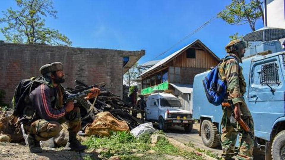 Security personnel stand guard during an encounter between security forces and militants at Drabgam in Pulwama District of South Kashmir.