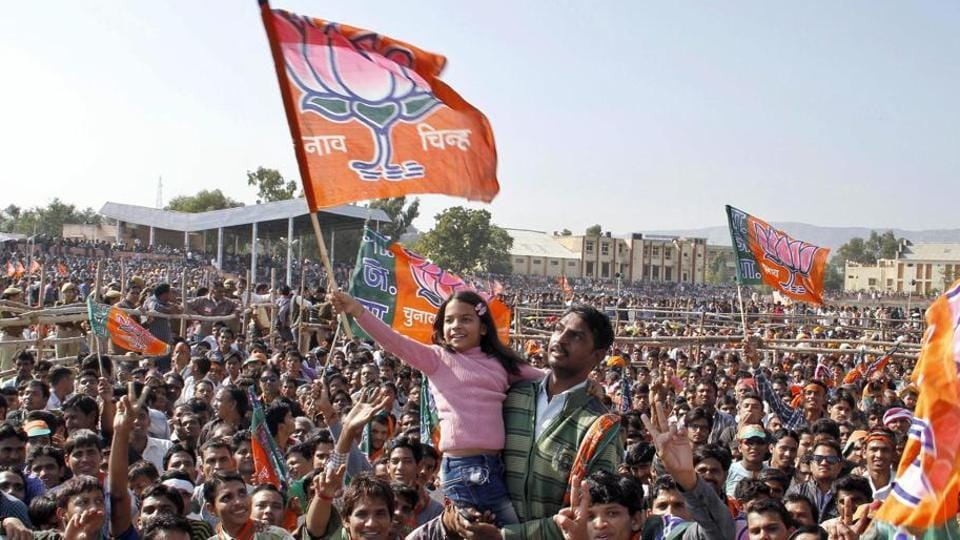 A child waves a BJP flag during a public meeting in Ajmer.