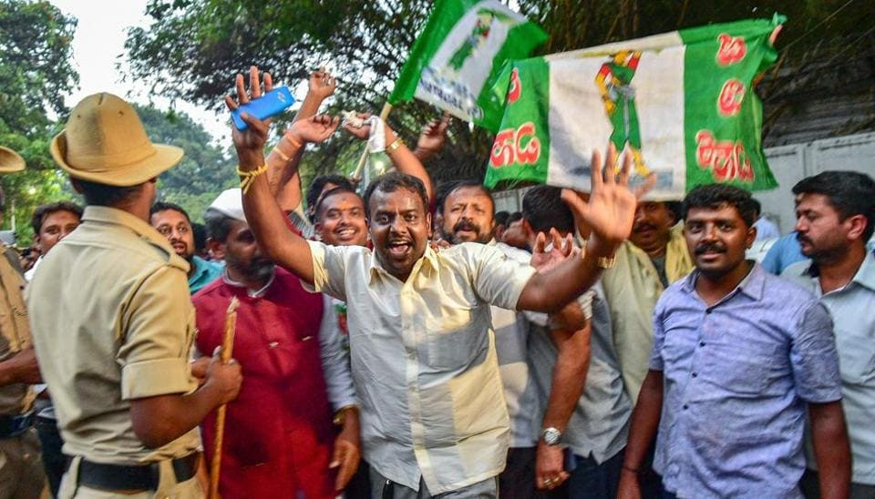 After the Karnataka election results, JD(S) workers celebrate outside the Raj Bhavan after the Congress extended support to it for government formation, in Bengaluru, on Tuesday.