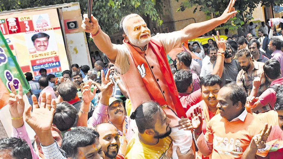 BJP supporters celebrate outside the party office after Karnataka poll results on Tuesday.