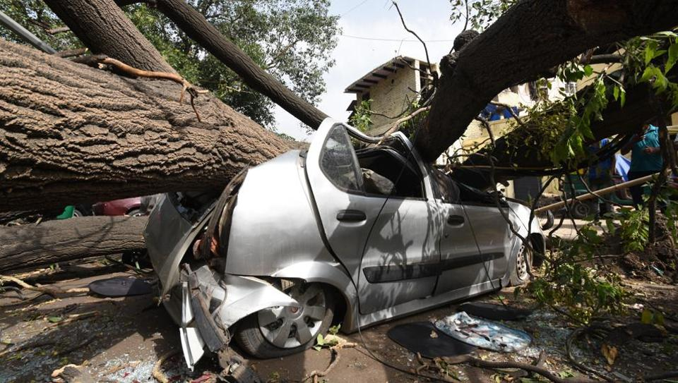 A large tree fell over a car near Minto Road, after an overnight dust storm hit the national capital in the early hours of Wednesday. The Indian Meteorological Department forecast more thunderstorms and squalls for the north and northwest regions of the country till Friday. (Arvind Yadav / HT Photo)