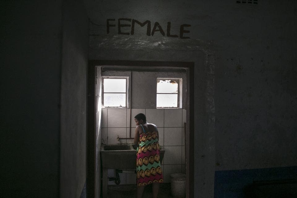 "A woman washes clothing in the bathroom of an abandoned building occupied by mostly Malawian migrants. The state has the money and land and should provide housing at affordable prices, according to Stuart Wilson, the executive director of the Socio-Economic Rights Institute of South Africa, calling the city ""not particularly keen"" on public housing. (Bram Janssen / AP)"