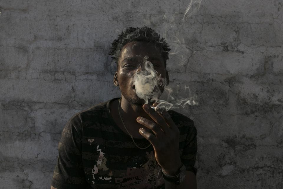 Malawian migrant Jonas smokes marihuana on a rooftop. For now, tens of thousands of squatters, and others who say they pay nominal rents, are left in a filthy limbo without basic services and at the mercy of Johannesburg's high rate of crime. Residents say they are disgusted by their living conditions. (Bram Janssen / AP)