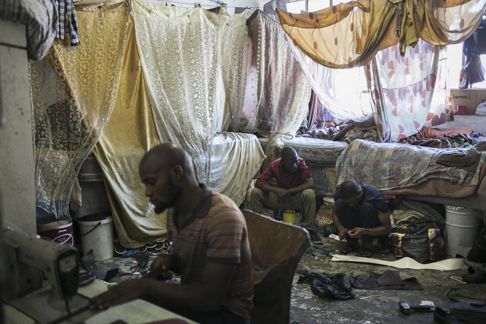 Malawian migrant shoe makers work inside their bedroom inside an abandoned building they occupy in downtown Johannesburg. Squatters say they want to see redevelopment that would give them a proper home, not force them to leave. (Bram Janssen / AP)