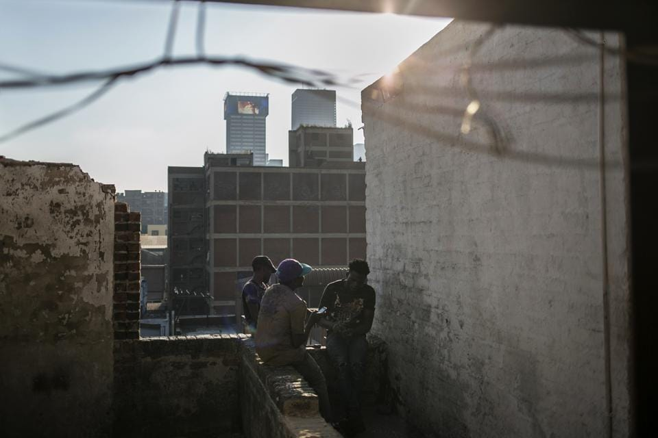 "Malawian migrants sit on the rooftop of an abandoned building. Mayor Herman Mashaba has alarmed residents of South Africa's largest city of more than 4.4 million people by accusing migrants from other countries for making up the majority of squatters, contributing to the xenophobia that periodically flares into violent attacks. Foreigners ""are not the responsibility of the city,"" he said last year. (Bram Janssen / AP)"