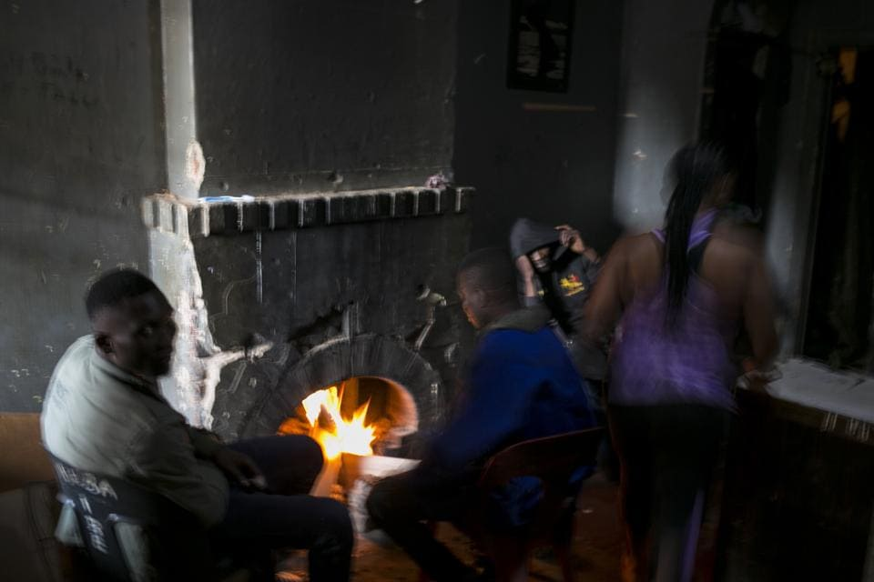 People warm themselves by a fire place in an abandoned building they occupy in downtown Johannesburg. Some squatters work as security guards, domestic workers and small traders in neighbourhoods nearby, while others are unemployed, hustle or turn to crime. (Bram Janssen / AP)