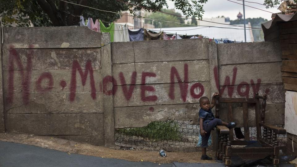 A toddler stands in front of a graffitied wall at an abandoned building occupied by squatters in downtown Johannesburg, South Africa. The city wants squatters cleared out to make way for an urban revival, with proposals to expropriate buildings and turn them over to private developers. (Bram Janssen / AP)