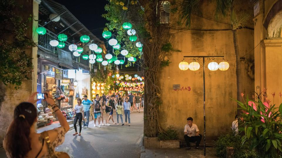 A man sits as tourists walk by in the old town of Hoi An, Qung Nam Province, Vietnam.