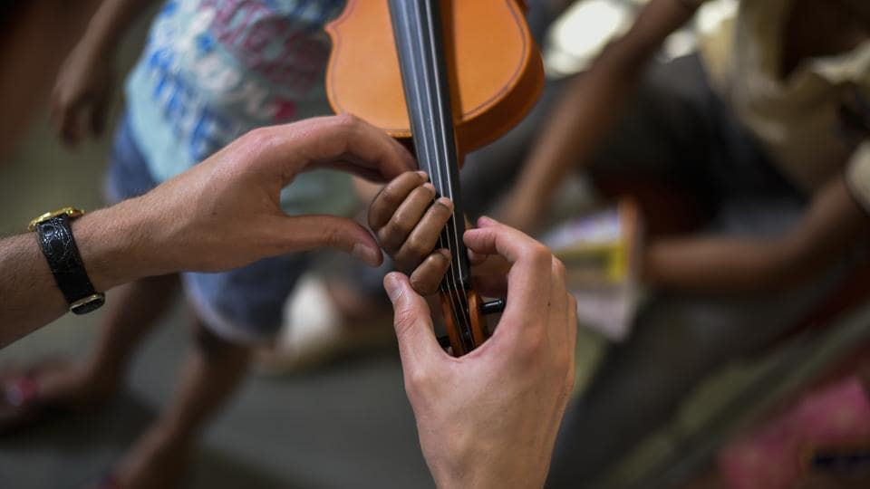 Pajak  helps Riya build pressure on a violin's strings. The project sponsors the cost of the violins for the children, their tuitions and also aims to facilitate higher education in music if the children wish to pursue the path. (Burhaan Kinu / HT Photo)