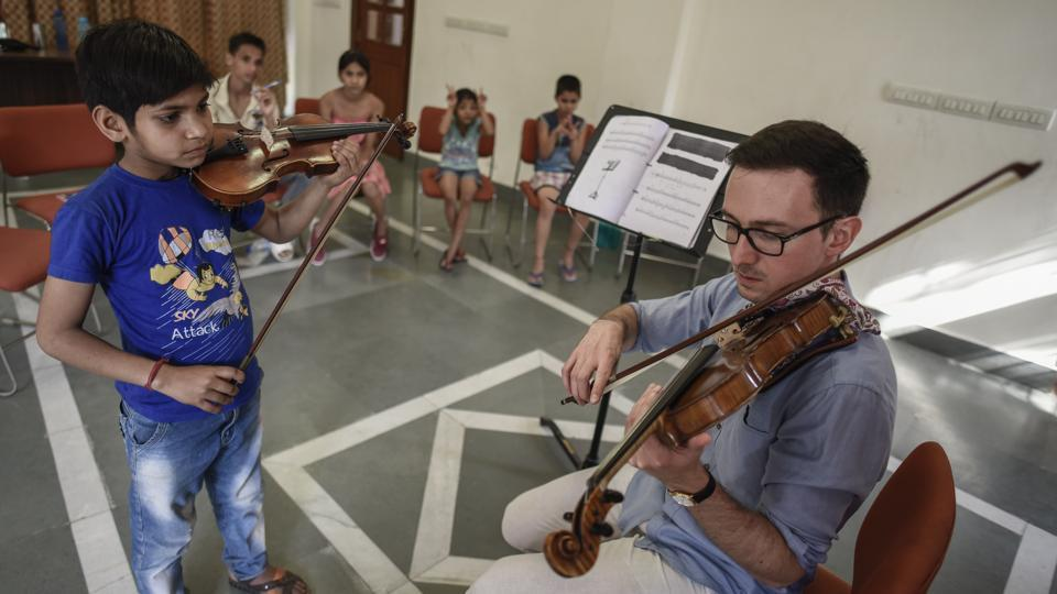 Ankush (L) and other students observe as their teacher Tomasz Pajak  demonstrates on the violin. A teacher with the Delhi School of Music, Pajak is a Polish violinist and has been conducting weekly group and individual lessons with this group of children. (Burhaan Kinu / HT Photo)