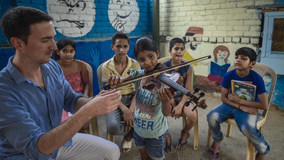 Riya, a Class 2 student plays the violin while other students and their instructor look on during music lessons for underprivileged children at Sanjay Camp in New Delhi. The project is being run by the Neemrana Music Foundation in collaboration with the Light Up, an NGO that works on emotional intelligence in the area. (Burhaan Kinu / HT Photo)