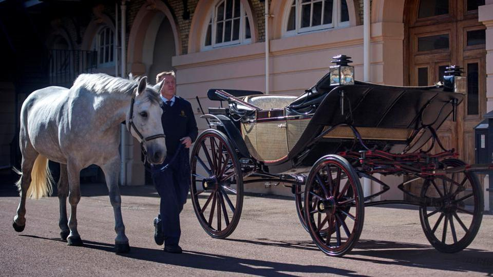 Philip Barnard-Brown, Senior Coachman at the Buckingham Palace Mews, leads a Windsor Grey, one of the horses that will pull the carriage at today's wedding, past the Ascot Landau carriage which is the centre piece of the celebratory procession around Windsor. (Victoria Jones / REUTERS)