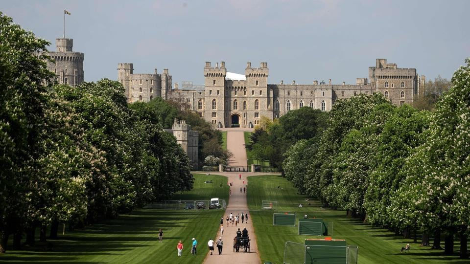 People walk along the Long Walk leading up to Windsor Castle. The Long Walk will be lined with well-wishers waiting to greet the royal couple as they pass by heading back to the castle at the end of the carriage procession after the ceremony. (Daniel Leal-Olivas / AFP)