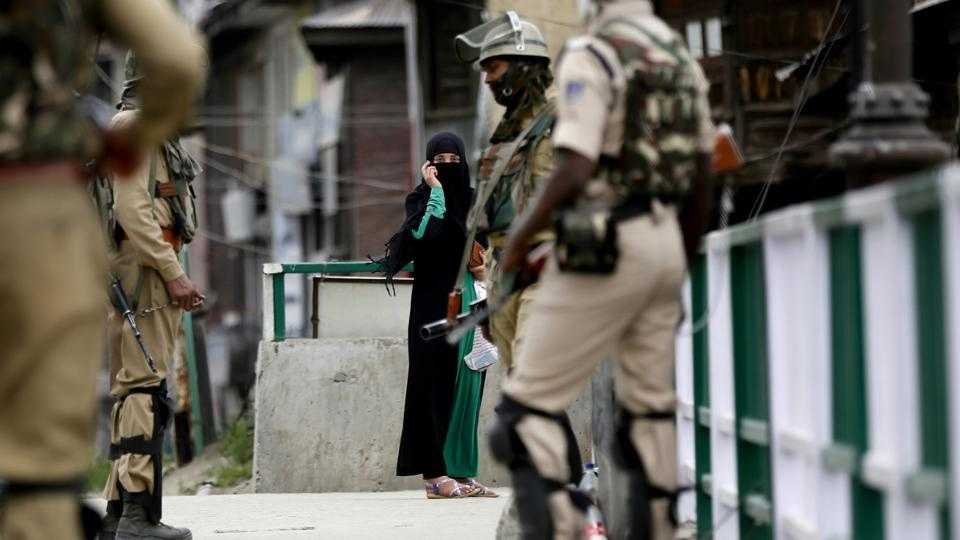 A Kashmiri woman looks at paramilitary soldiers standing guard on the first day of the holy month of Ramadan in on May 17.
