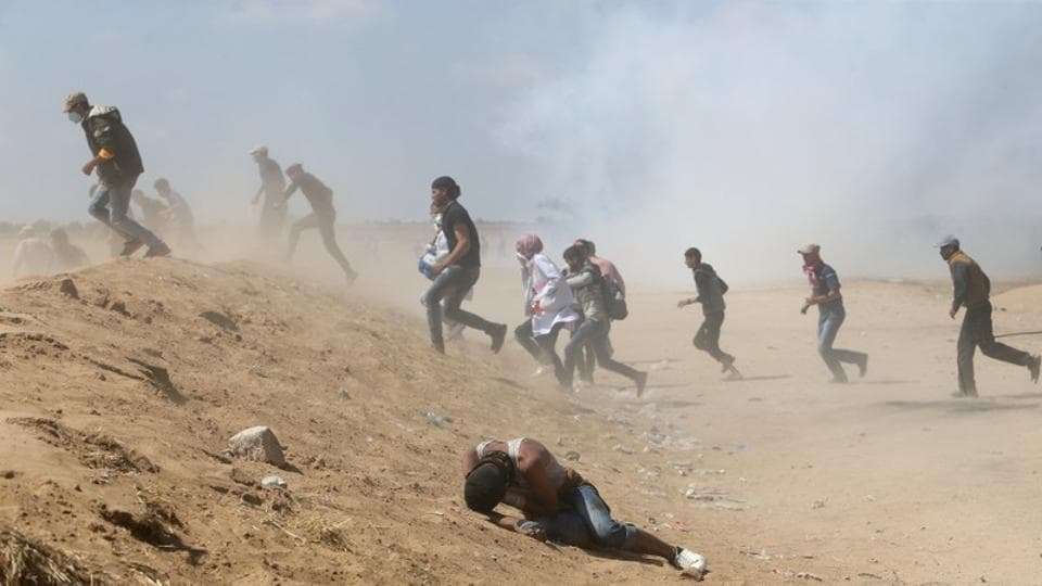 A Palestinian demonstrator reacts as others run from tear gas fired by Israeli forces during a protest marking the 70th anniversary of Nakba, at the Israel-Gaza border in the southern Gaza Strip May 15, 2018.