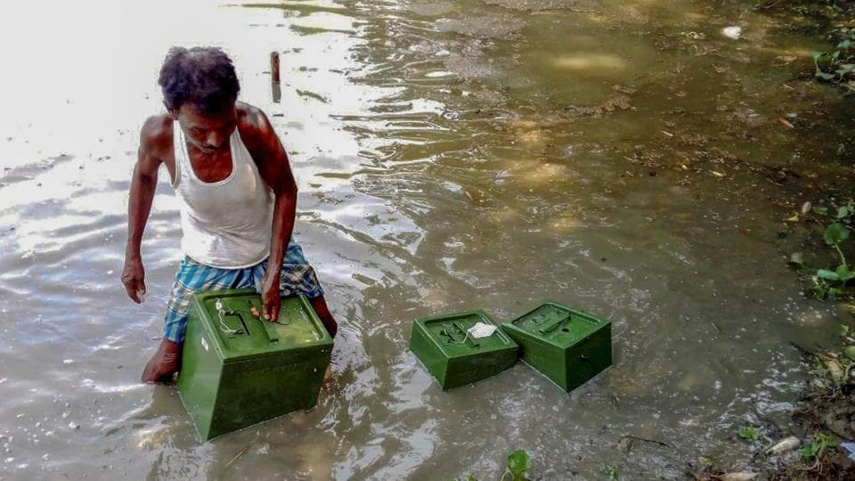 A man collects ballot boxes from a pond thrown by some unknown people during panchayat elections in West Bengal, in Memari of Burdwan district on Monday.