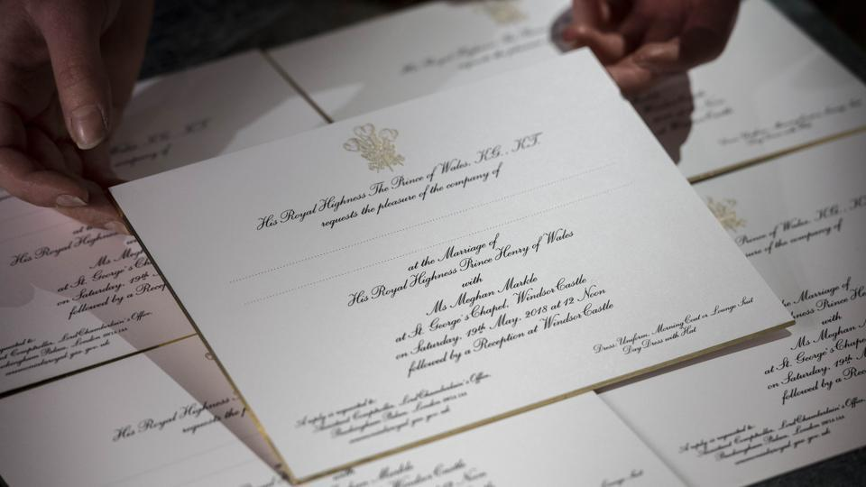Hands hold freshly printed invitations for Prince Harry and Meghan Markle's wedding at a workshop of Barnard and Westwood who have held the Royal Warrant for Printing and Bookbinding since 1943. Using American ink on English card, the invitations were printed in gold and black, then burnished and gilded around the edge. (Victoria Jones / WPA Pool / Getty Images)
