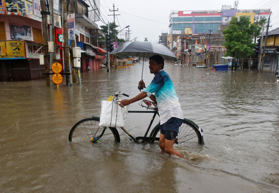 People walk through a waterlogged street after heavy rainfall in Agartala on Friday. At least four people, including a child and a woman, were killed early on Friday in mud house collapses in two incidents in West Tripura district of Tripura after the downpour. (Jayanta Dey / REUTERS)