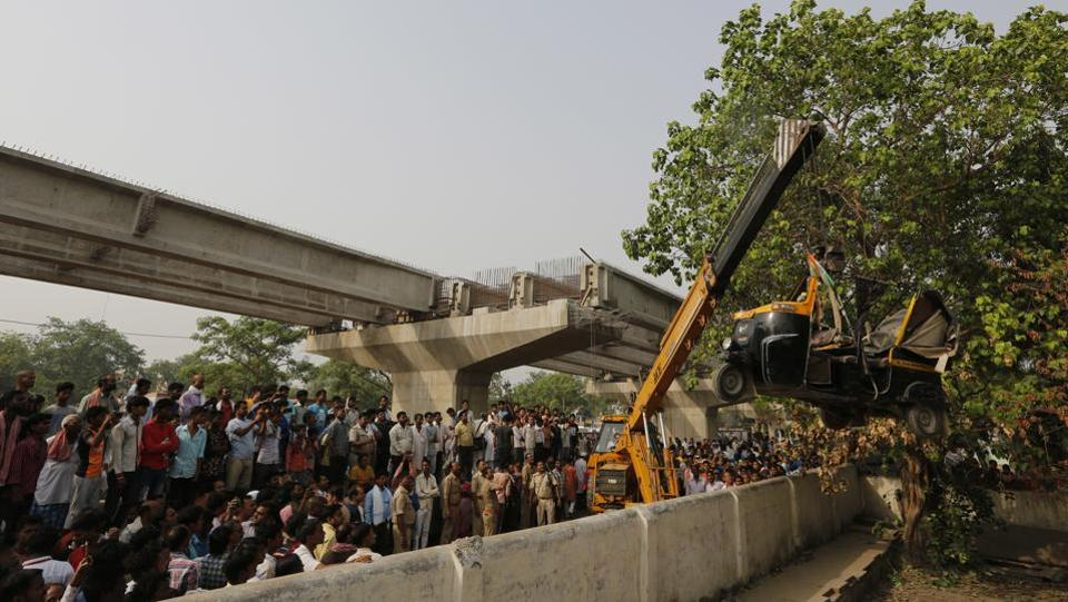 A crane is used to lift an auto rickshaw that got crushed after a highway overpass being built collapsed in Varanasi, Uttar Pardesh, on May 16, 2018. (Rajesh Kumar Singh / AP)