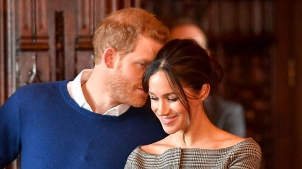 Britain's Prince Harry whispers to Meghan Markle as they watch a performance by a Welsh choir in the banqueting hall during a visit to Cardiff Castle in Cardiff, Britain.