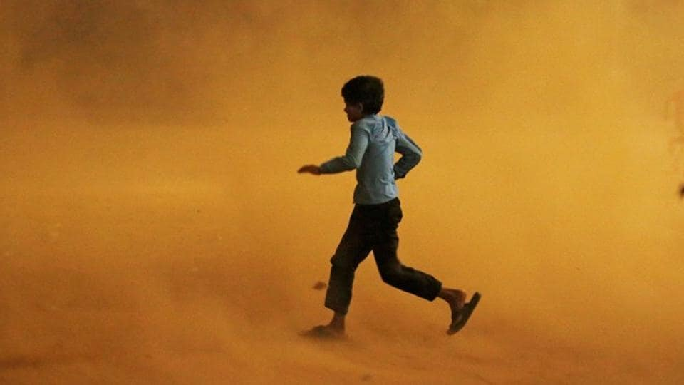 A boy runs for cover during a dust storm in New Delhi, on May 13, 2018. (Adnan Abidi / REUTERS)