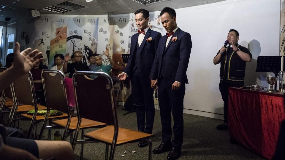 Pastor Joe Pang prays behind C.P. So (L) and Alvin Chan (R) during their wedding ceremony at a church in Hong Kong. It was a day Chan and his partner So had never imagined possible -- tying the knot in front of cheering family and friends in Hong Kong. (Dale De La Rey / AFP)