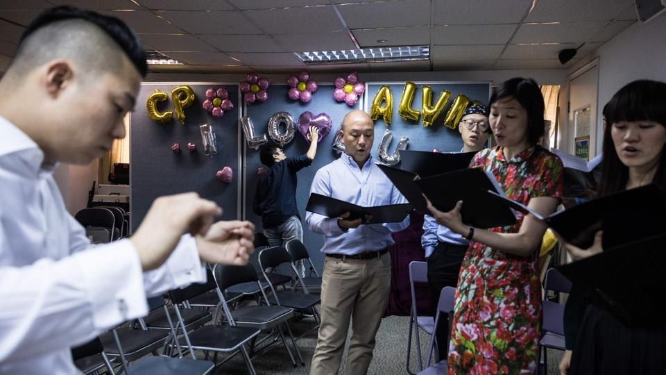 Choir members rehearse as a man sets up balloons before the ceremony. Apprehensive about holding their wedding ceremony in the socially conservative city a year after they signed marriage papers in Britain, Chan and So were finally convinced by their pastor to hold a small-scale celebration. (Dale De La Rey / AFP)