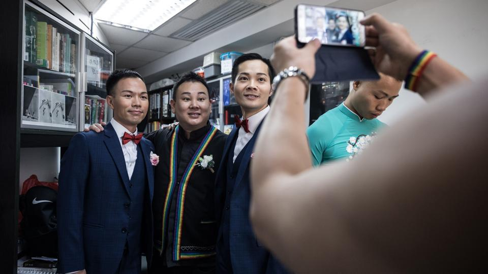 C.P. So (centre R) and Alvin Chan (L) pose for a photograph with pastor Joe Pang before their ceremony. Like many other gay weddings in Hong Kong, this one was held behind closed doors, tucked away in a commercial space. Same-sex marriage is not legally recognised in Hong Kong and often those who have a ceremony say they prefer to do it away from the public gaze. (Dale De La Rey / AFP)