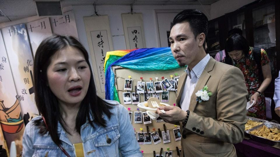 Guests eat next to a board of Polaroid photographs. The Hong Kong government is currently appealing a landmark court decision to grant a British lesbian the spousal right to live and work in the territory. (Dale De La Rey / AFP)